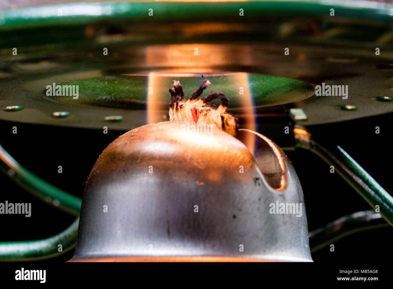 Old technology for interior lighting. Oil lamp, wick, kerosene in the photo. Dark background. - Stock Image