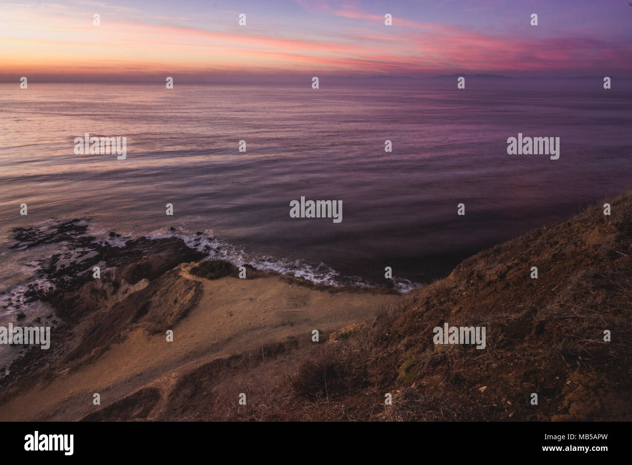 Long-exposure shot of smooth waves crashing into Flat Rock Point rock formations and Bluff Cove Trail after sunset, Palos Verdes Estates, California - Stock Image