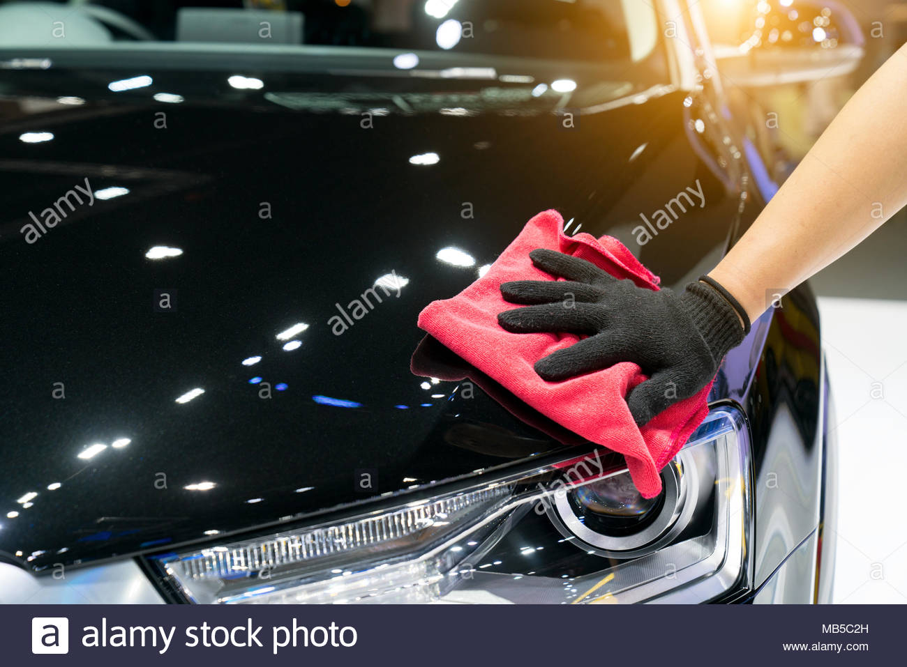 Car detailing - the man holds the microfiber in hand and polishes the car. Selective focus. Stock Photo