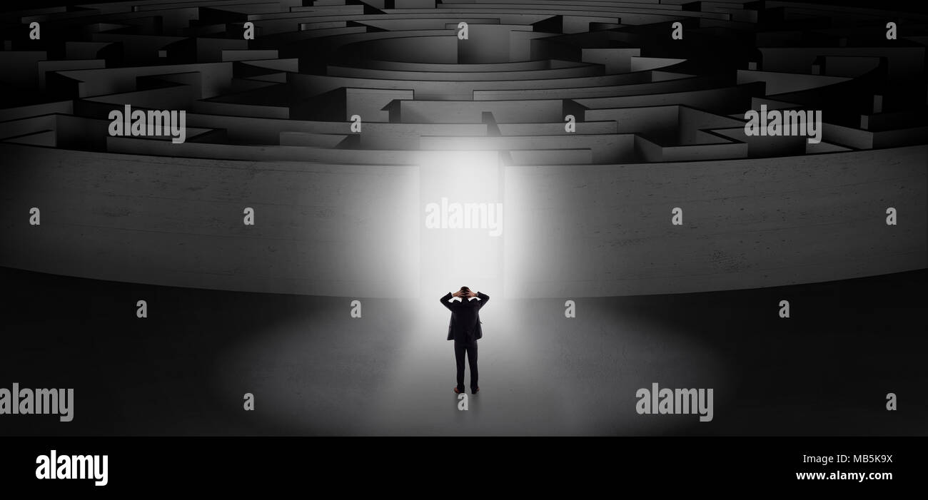 Businessman getting ready to enter a concentric labyrinth with lighted entrance concept  - Stock Image