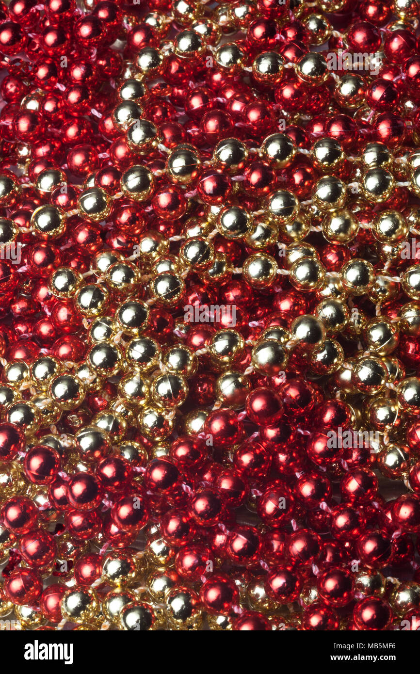 Still life of colorful round gold and red plastic beads - Stock Image
