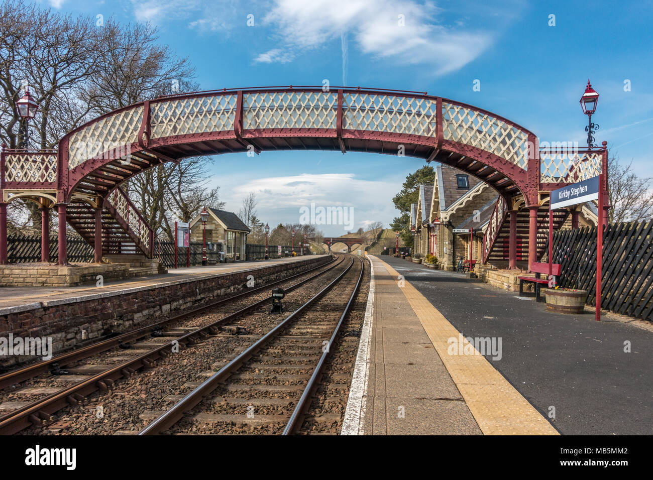 Looking down the salt gritted platform and railway tracks of Kirkby Stephen on a beautiful spring day, Yorkshire Dales - Stock Image