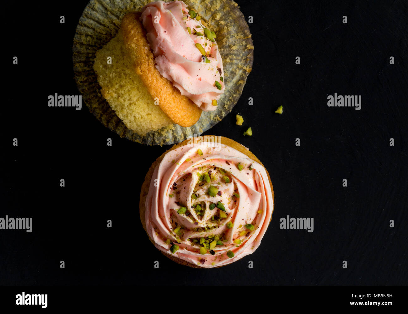 Two pink cup cakes with pistachio nut sprinkles on black background, top view photograph - Stock Image