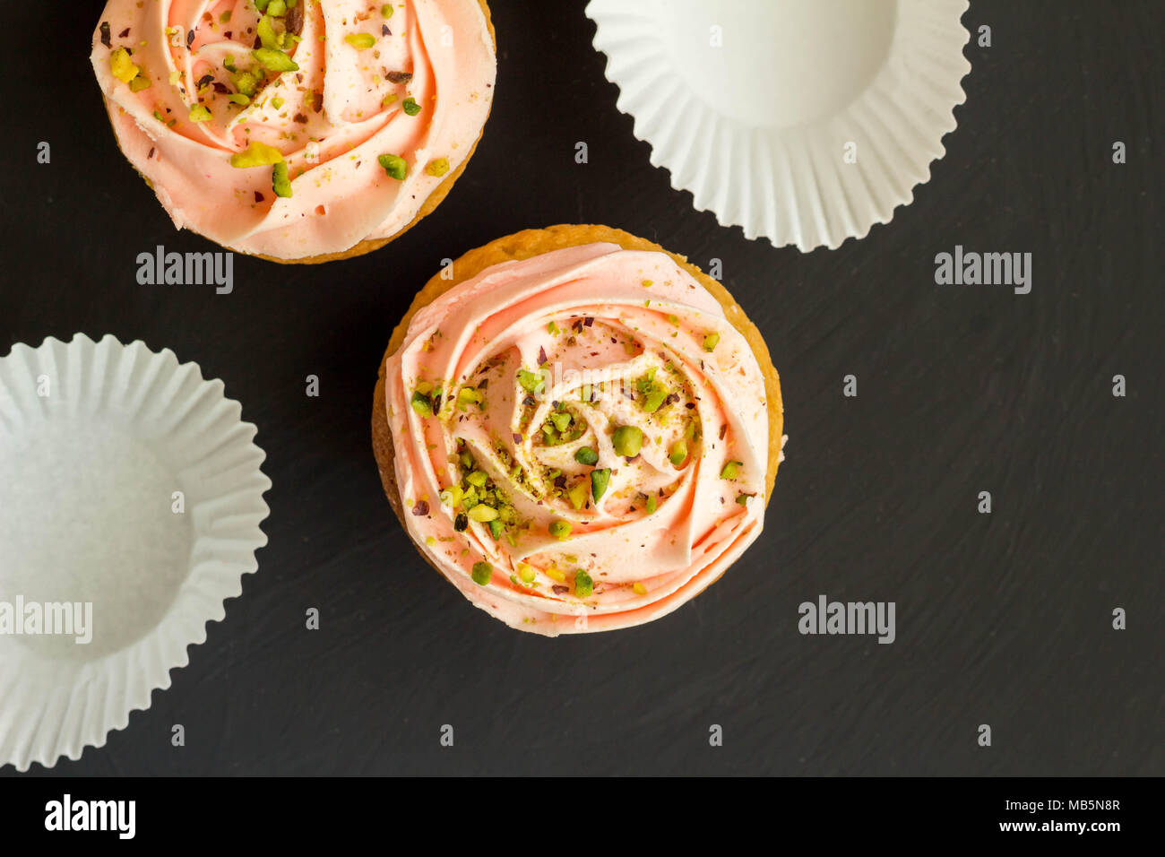 Two pink cup cakes close up on black background - Top view photo with space for text - Stock Image