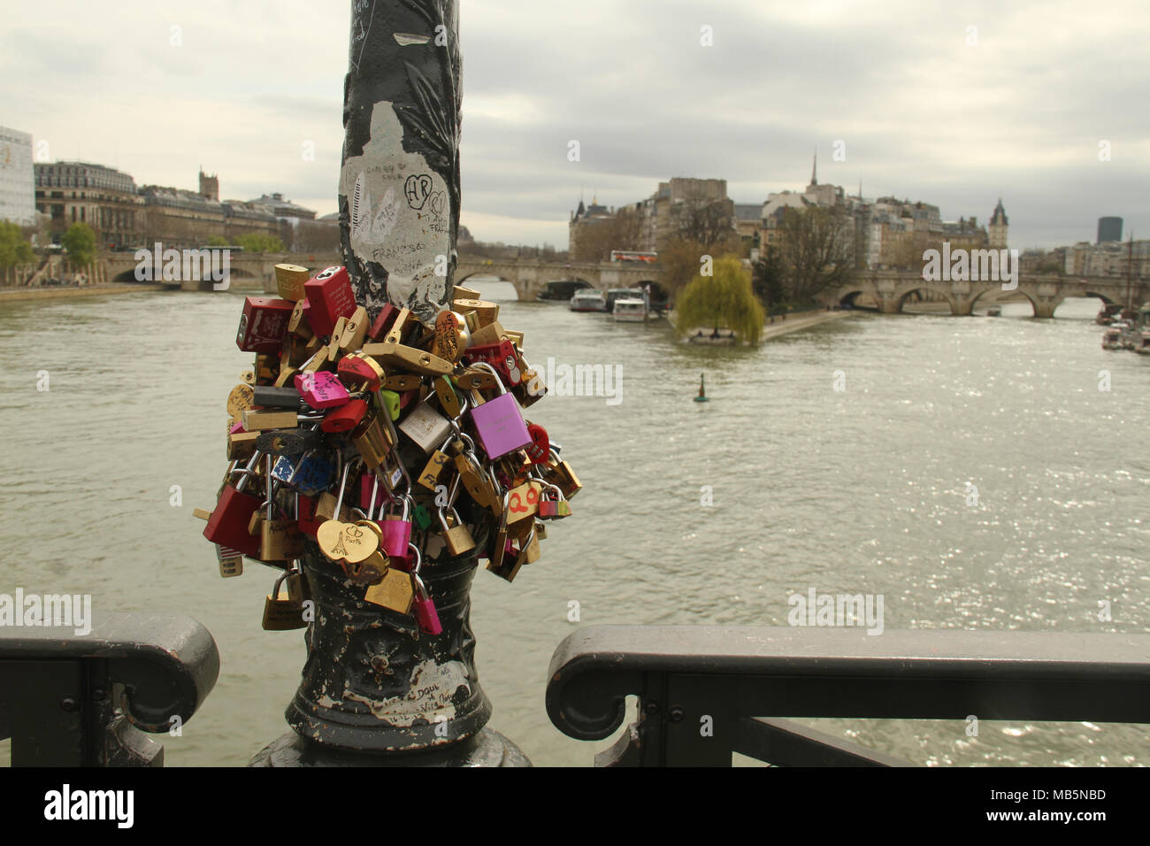 Paris, France -  03 April, 2018. Padlocks on a pole on the Pont des Arts bridge on 03 April 2018, with the river Seine seen on the background. The first Iron bridge built in France, had its railings replaced with glass panels after they collapsed under the weight on the metal padlocks. General view of Paris, France. @ David Mbiyu/Alamy Live News - Stock Image