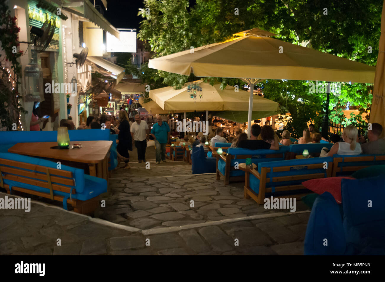 Tourists enjoying a warm evening on the steps of the Rock'n'Roll taverna, Skiathos, Greece. - Stock Image
