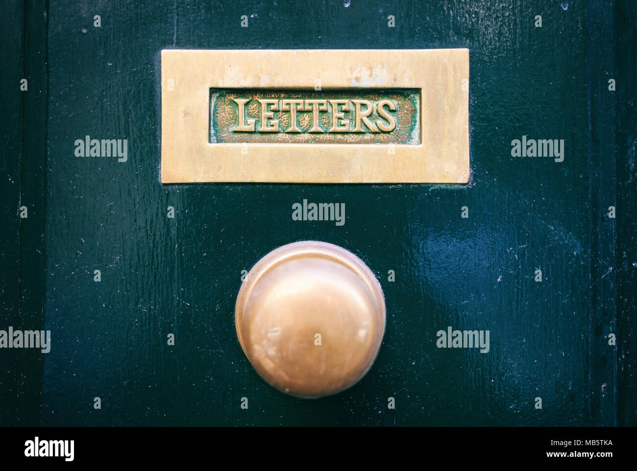 Old brass mail letter box and door knob on a green front door, text ...
