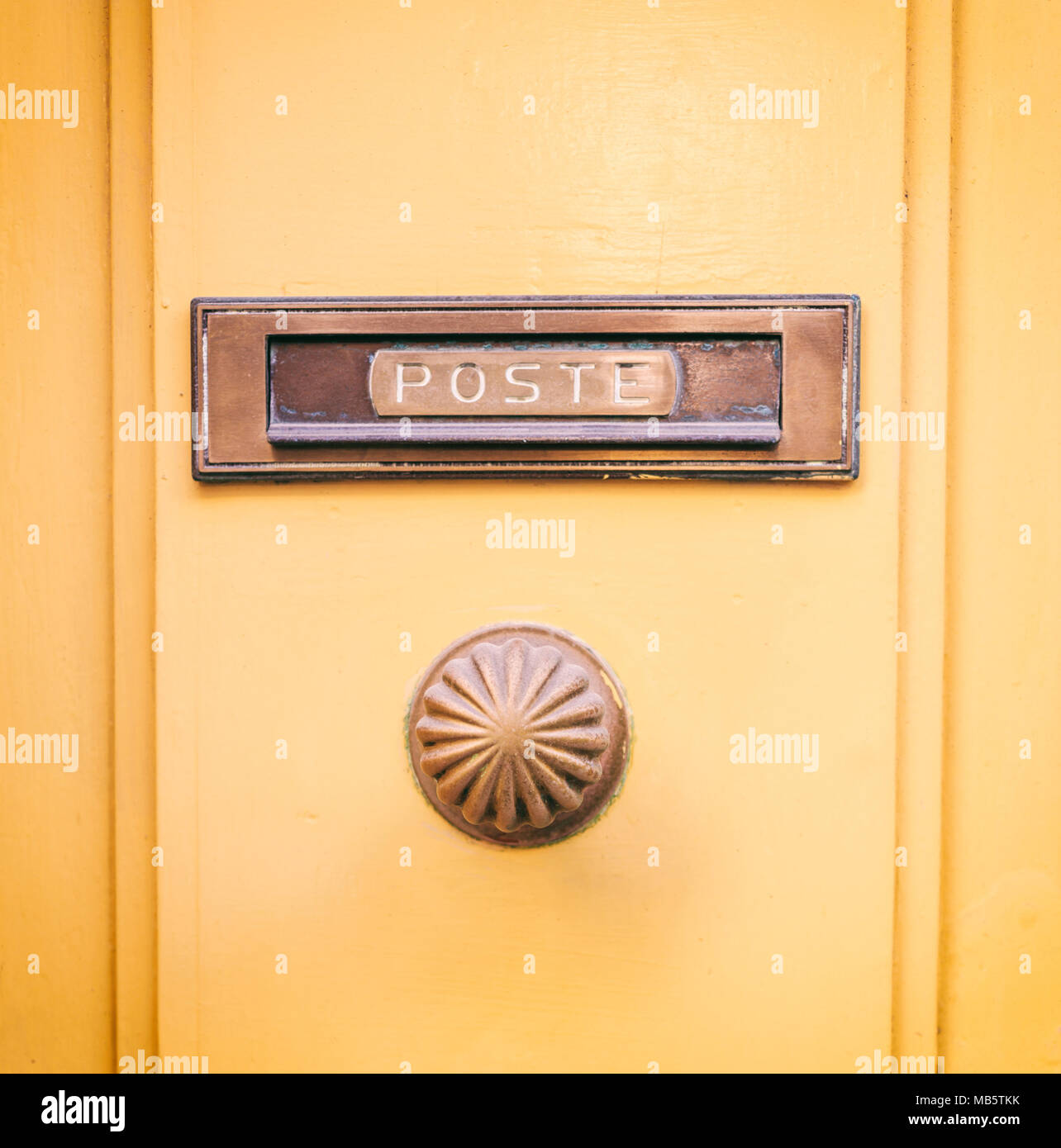 Old brass mail letter box and door knob on a yellow front door, text ...