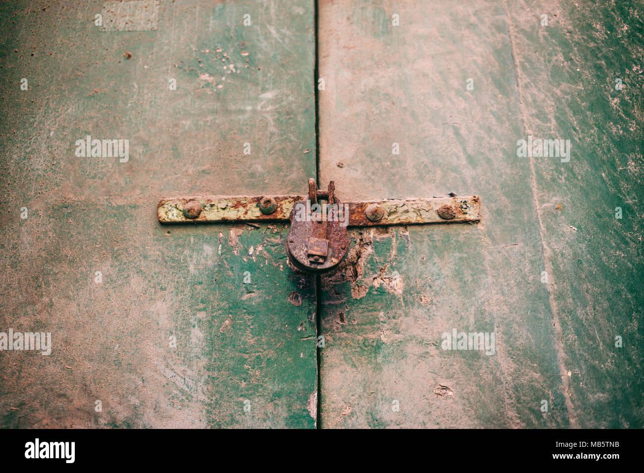 Locked door. Closed old rusty padlock on a damaged wooden door, closeup view Stock Photo