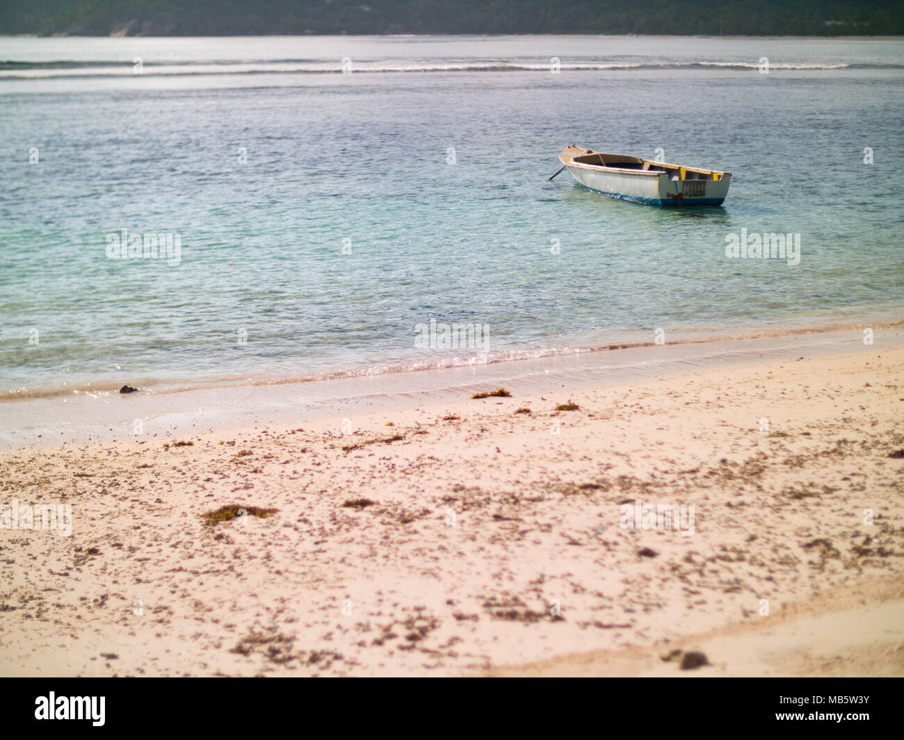 Small boat anchored off a Seychelles beach - Stock Image
