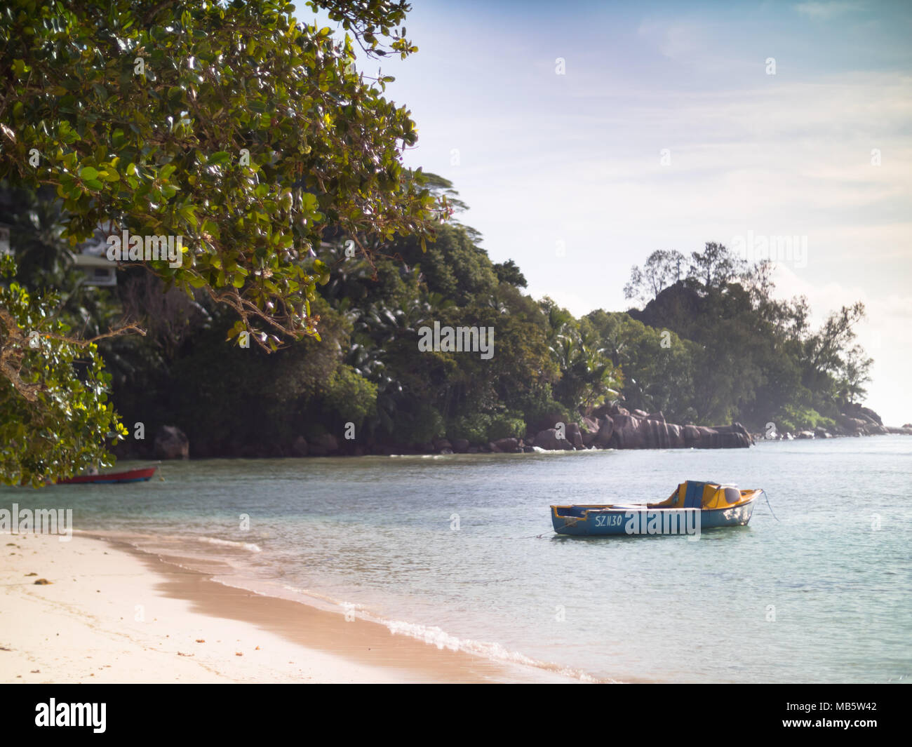 Small colorful boats anchored off a Seychelles beach - Stock Image
