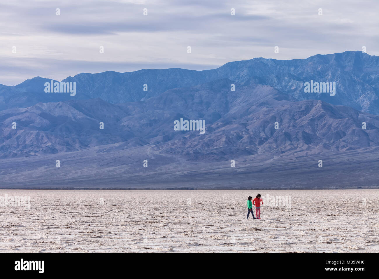 Two young kids were exploring the vast landscape at Badwater Basin in Death Valley National Park, California, United States. Stock Photo