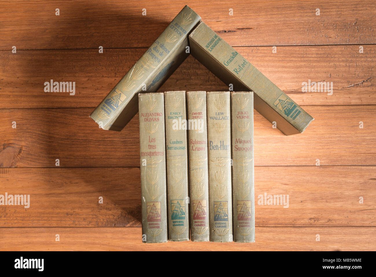 Stack of old books forming the figure of a house on some wooden boards. - Stock Image