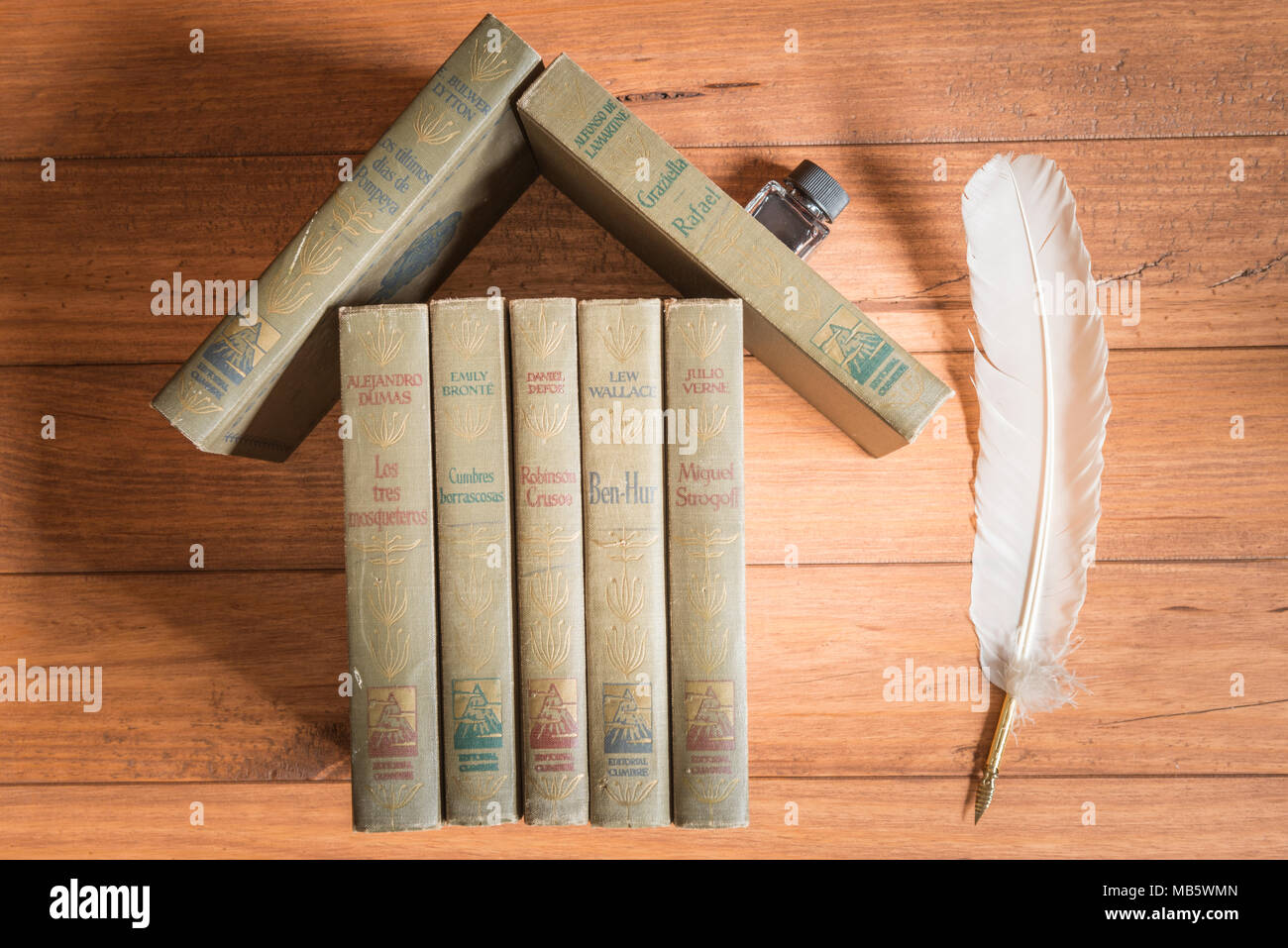 Stack of old books forming the figure of a house, with an inkwell like a fireplace and a feather like a tree, all on some wooden boards. - Stock Image