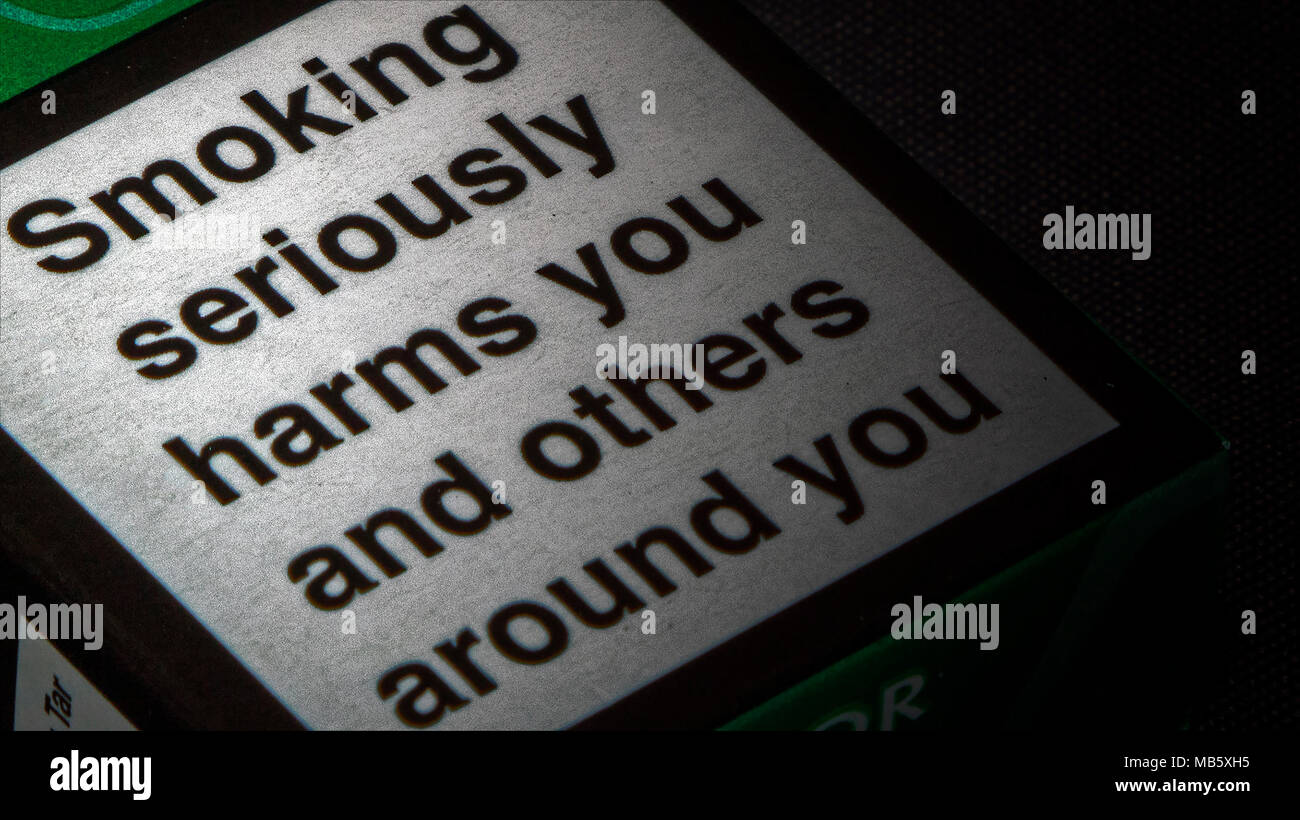 UK cigarette packet warning: 'Smoking seriously harms you and others around you.' - Stock Image