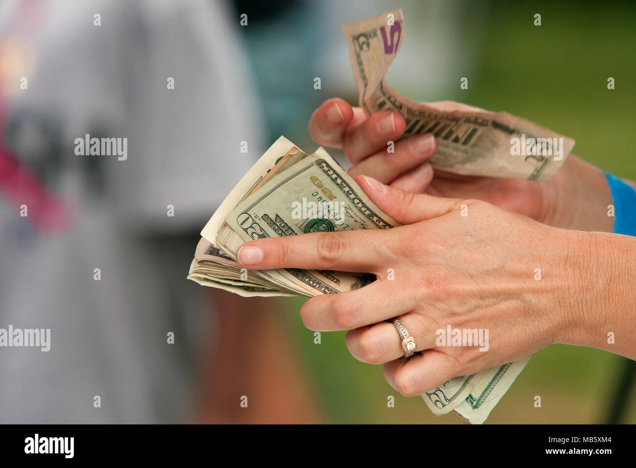 Closeup of a vendor's hands counting money to make change on a transaction at the Annual Atlanta Ice Cream Festival on July 27, 2013 in Atlanta, GA. - Stock Image