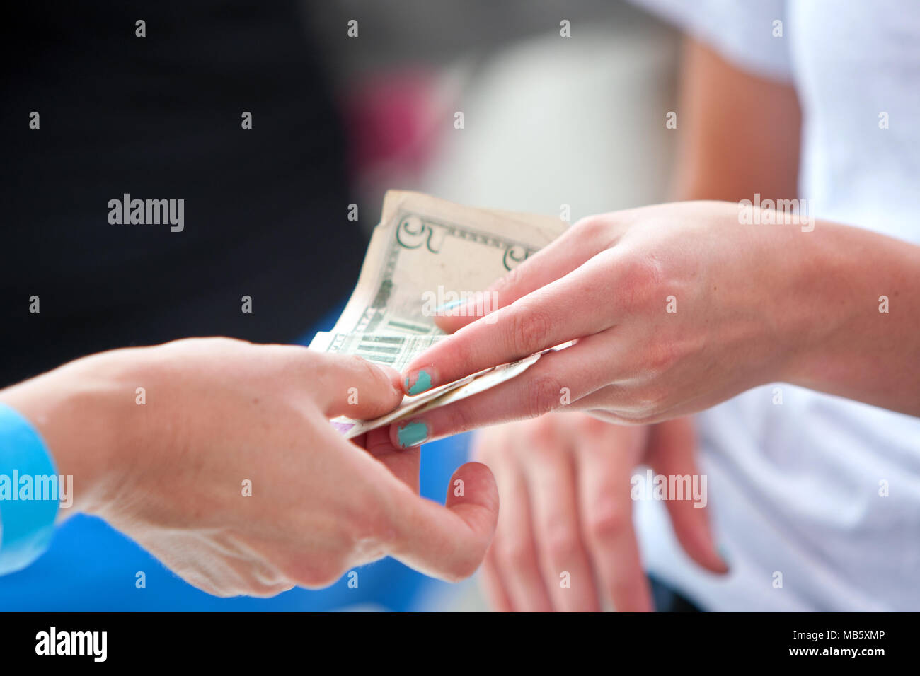 Closeup of two women's hands exchanging money at a vendor booth at the Annual Atlanta Ice Cream Festival on July 27, 2013 in Atlanta, GA. - Stock Image