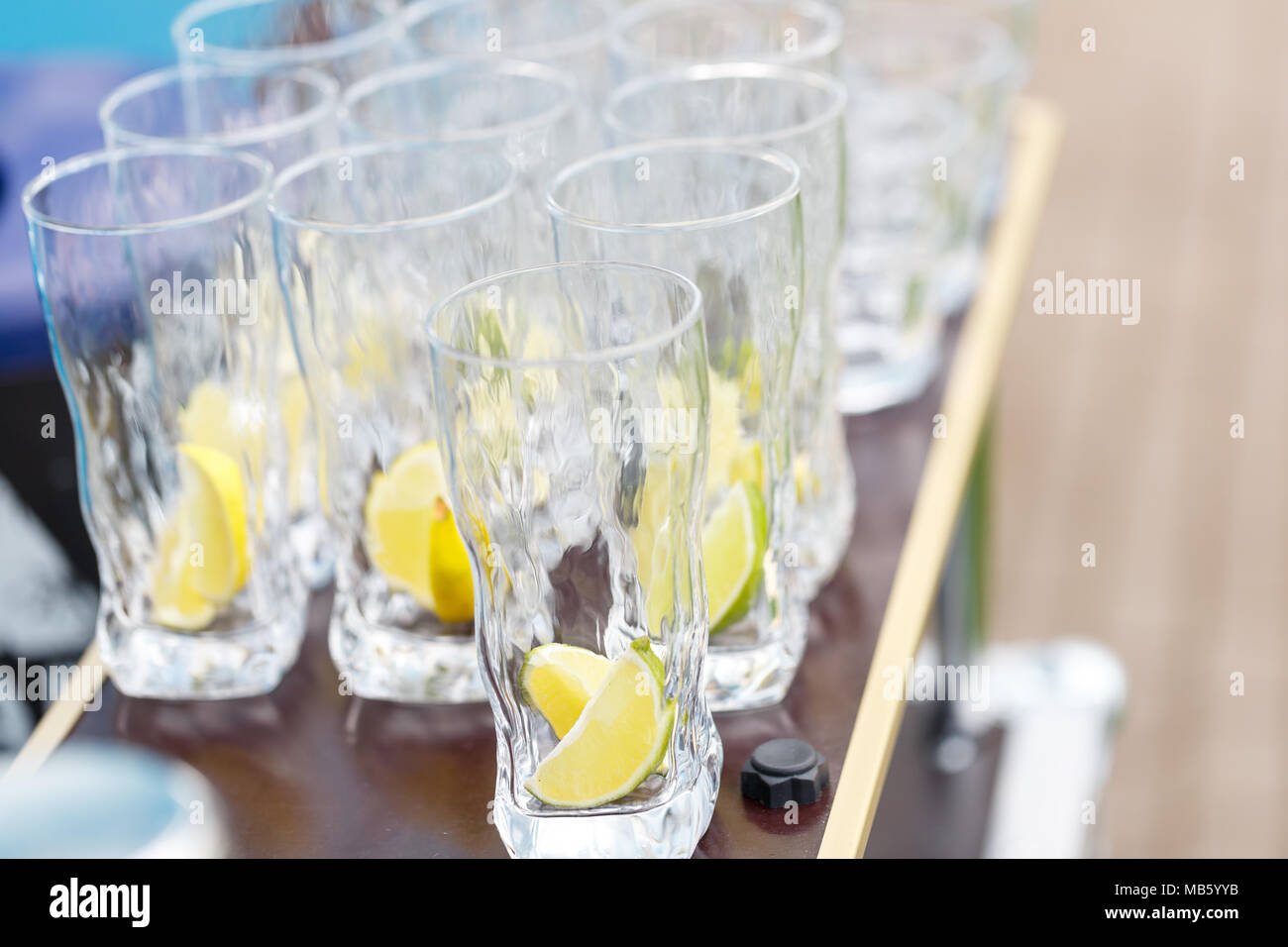 Glass for lemonade with sliced citrus fruits on a buffet table. Summer party outdoor. Detox. Stock Photo