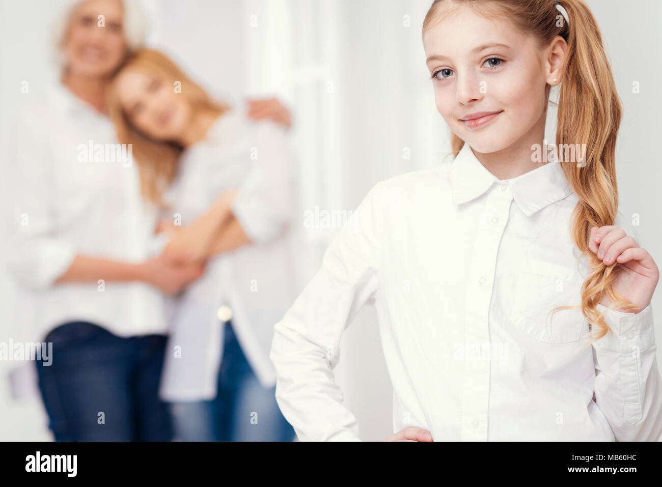 Adorable girl with ponytails smiling while family embracing in background - Stock Image