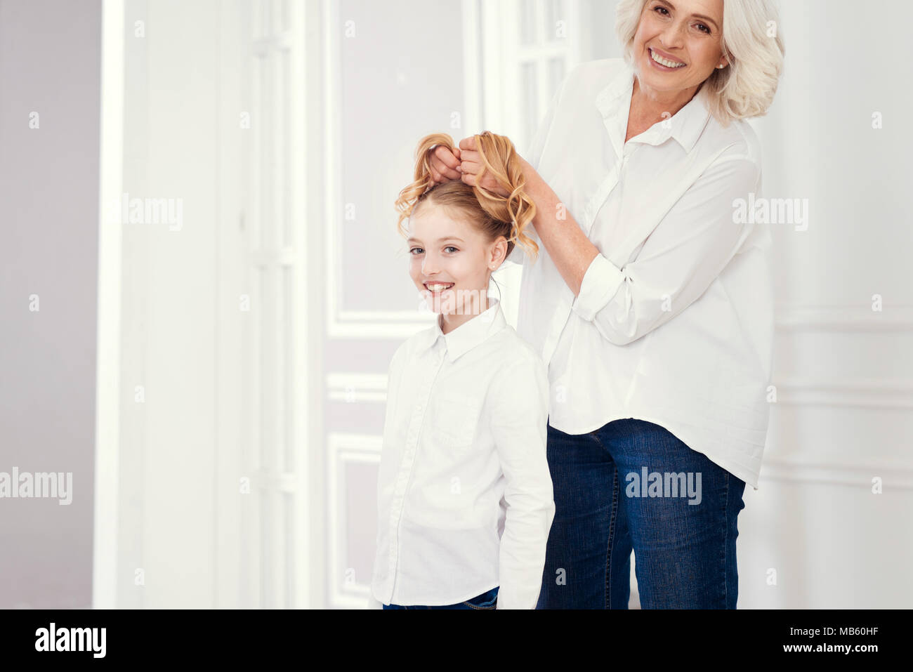 Careful hairdressing her preteen granddaughter at home - Stock Image