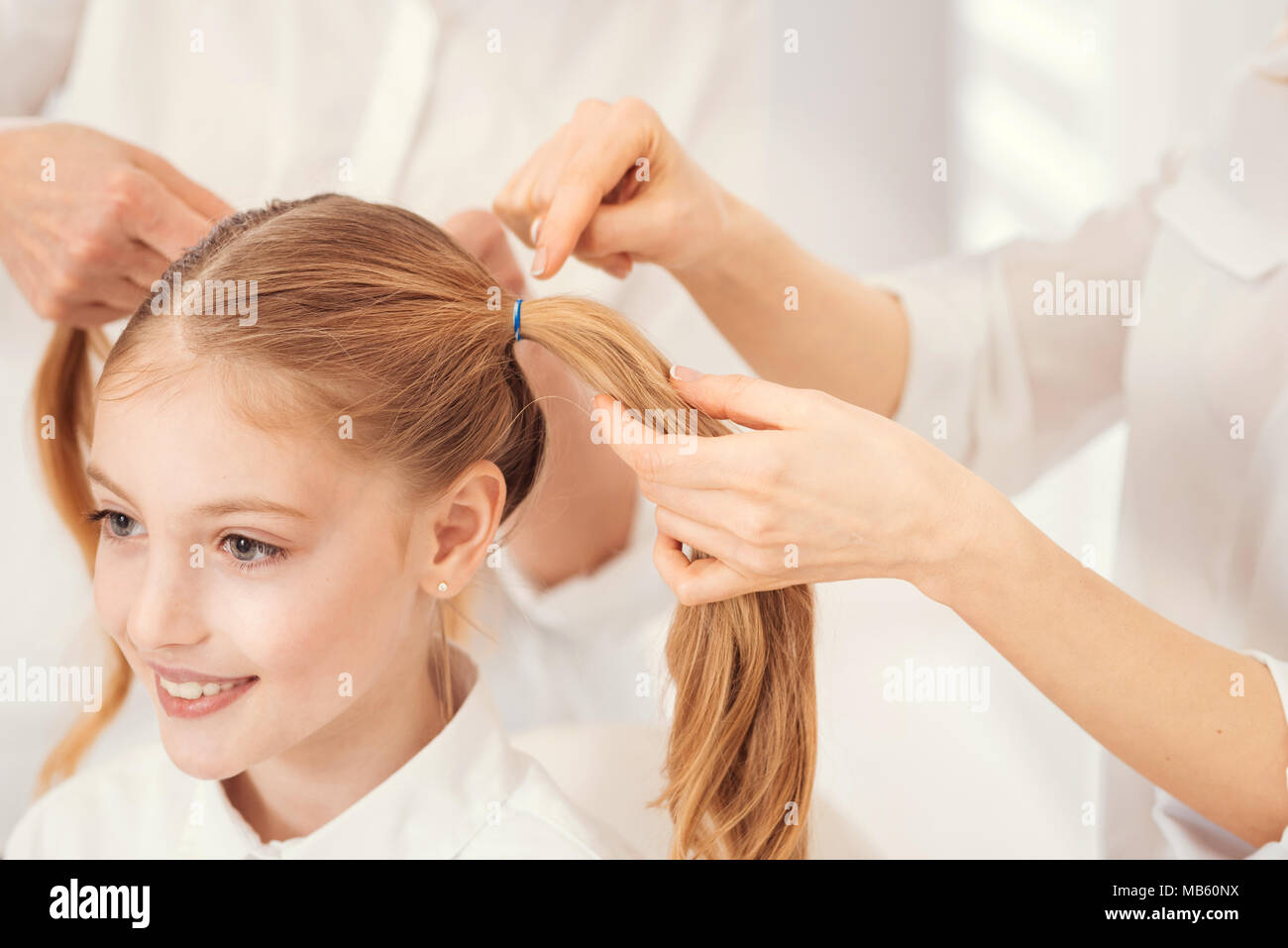 Close up of mother and granny making ponytails - Stock Image