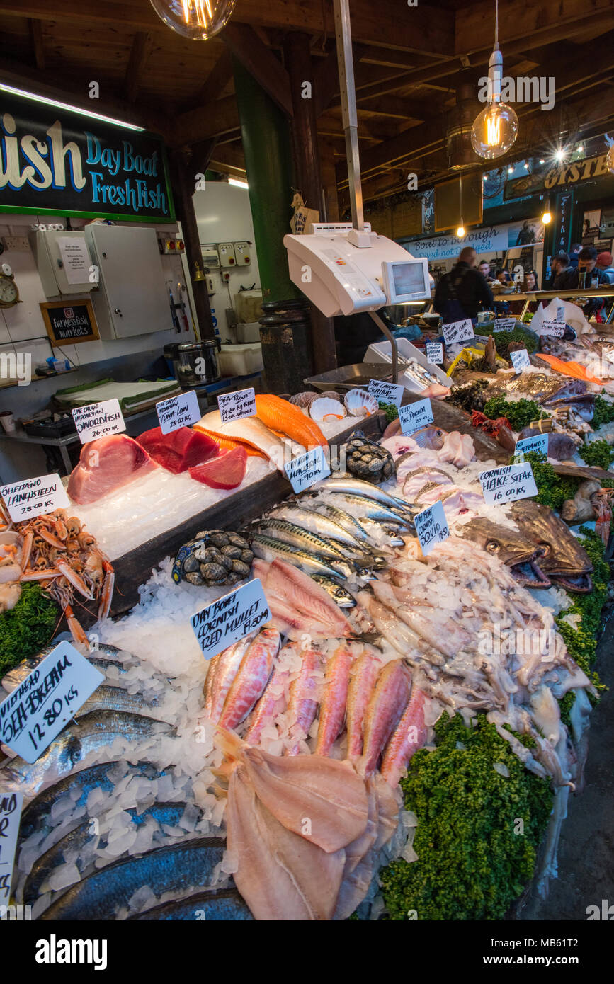 a fresh fish or fishmongers stall selling the catch of the day and fresh fish at borough market in central london. wet fish and healthy eating stall. - Stock Image