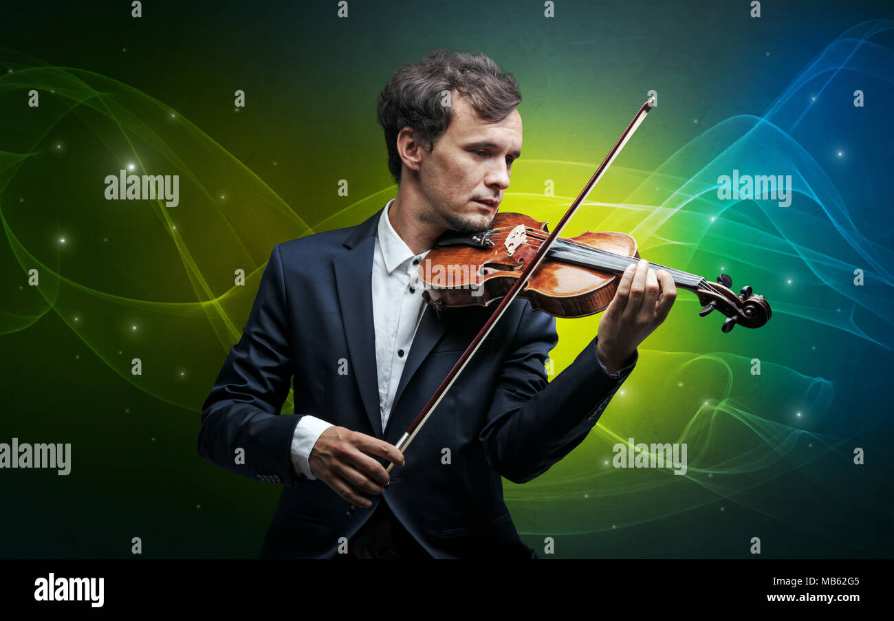 Serious classical violinist with fabled sparkling wallpaper - Stock Image