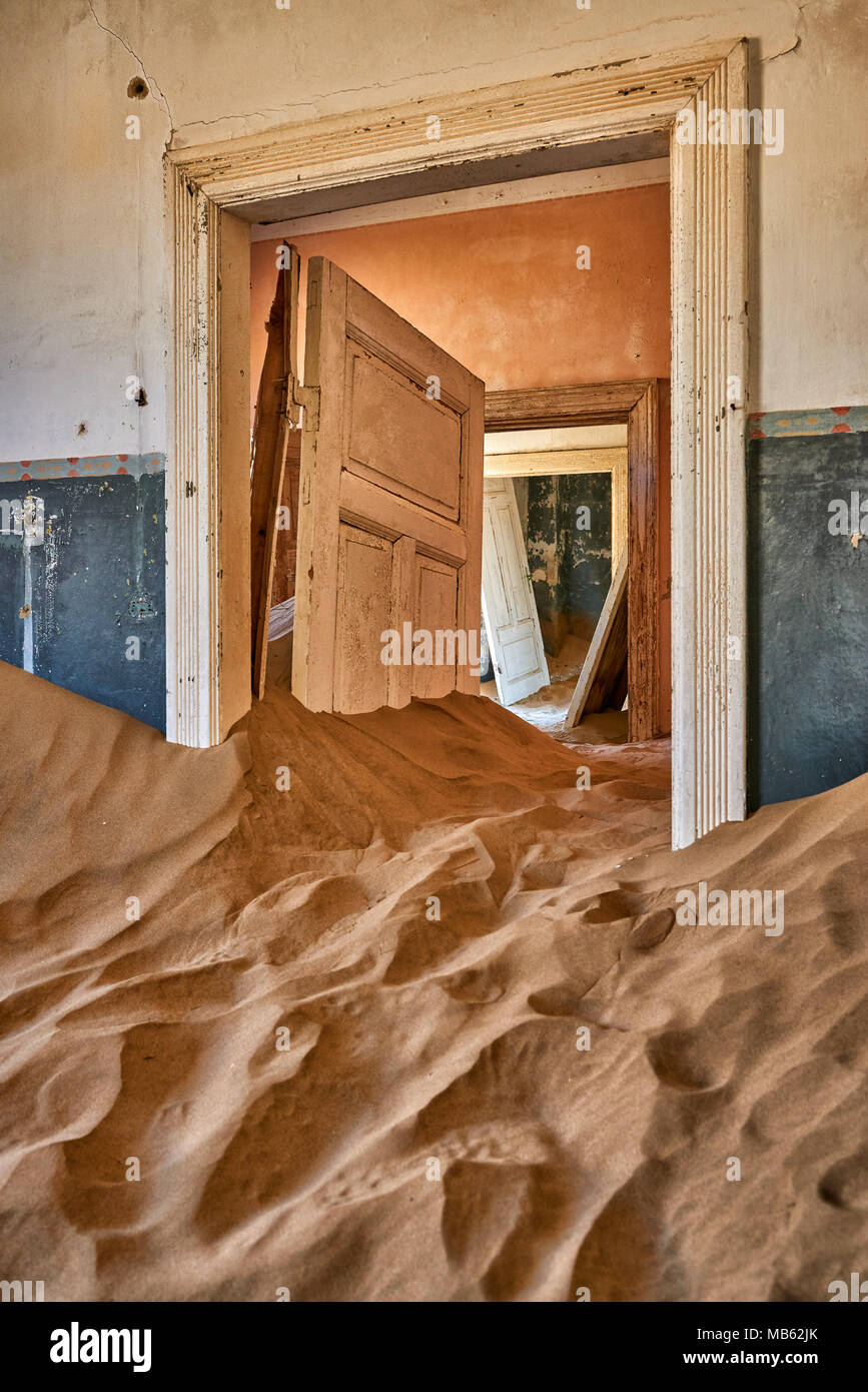view through doors of empty rooms filled with sand in Kolmanskop ghost town, Luderitz, Namibia, Africa - Stock Image