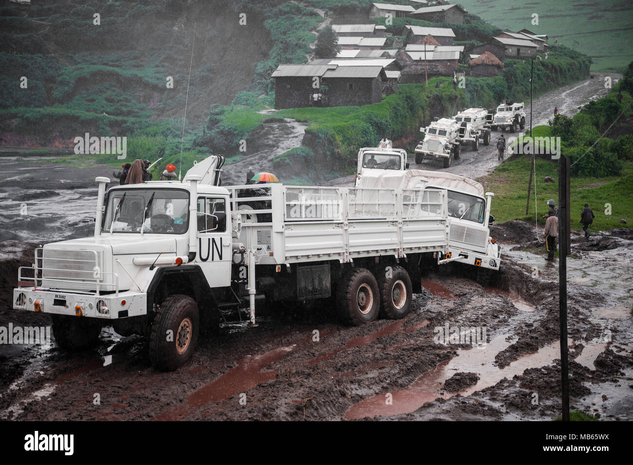 A convoy of South African UN peacekeepers struggle through the DRC roads enroute to Masisi. A truck attempts to tow another vehicle stuck in the mud - Stock Image