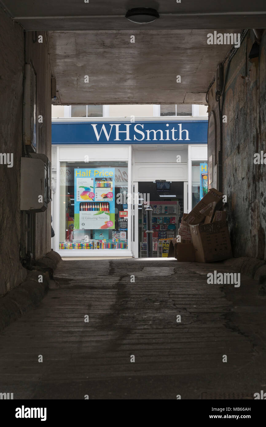 Death of the High Street metaphor / concept - WHSmith Bodmin (Cornwall) seen through archway opposite shop. High Street crisis, WH Smith rent cut plea Stock Photo