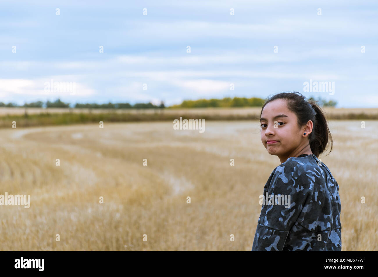 Young Girl Exploring in a Field after a Harvest - Stock Image