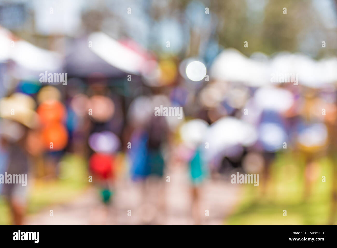 Blur abstract people background, unrecognizable silhouettes of people walking on outdoor festival fair. Food stall at day festival for background usag Stock Photo