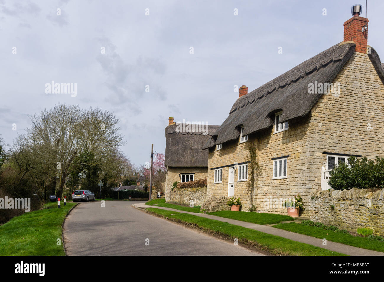 A view of the main street in the pretty village of Ravenstone, Buckinghamshire, UK; with thatched and stone built properties lining. Stock Photo