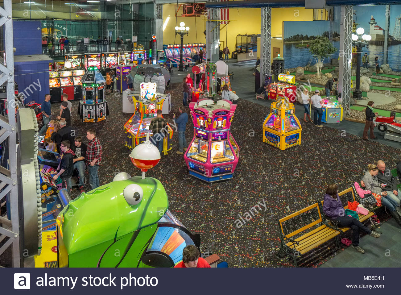 People play at various amusements in the video arcade of Adventure Zone of Canal Park, Duluth, Minnesota. - Stock Image