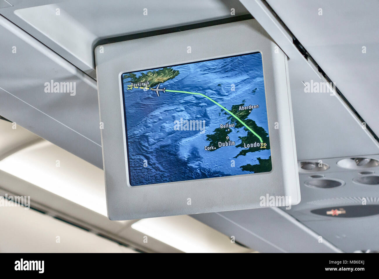 Interior of a British Airways Airbus A320 aircraft, showing a monitor screen displaying the flight path from London to Reykjavik - Stock Image