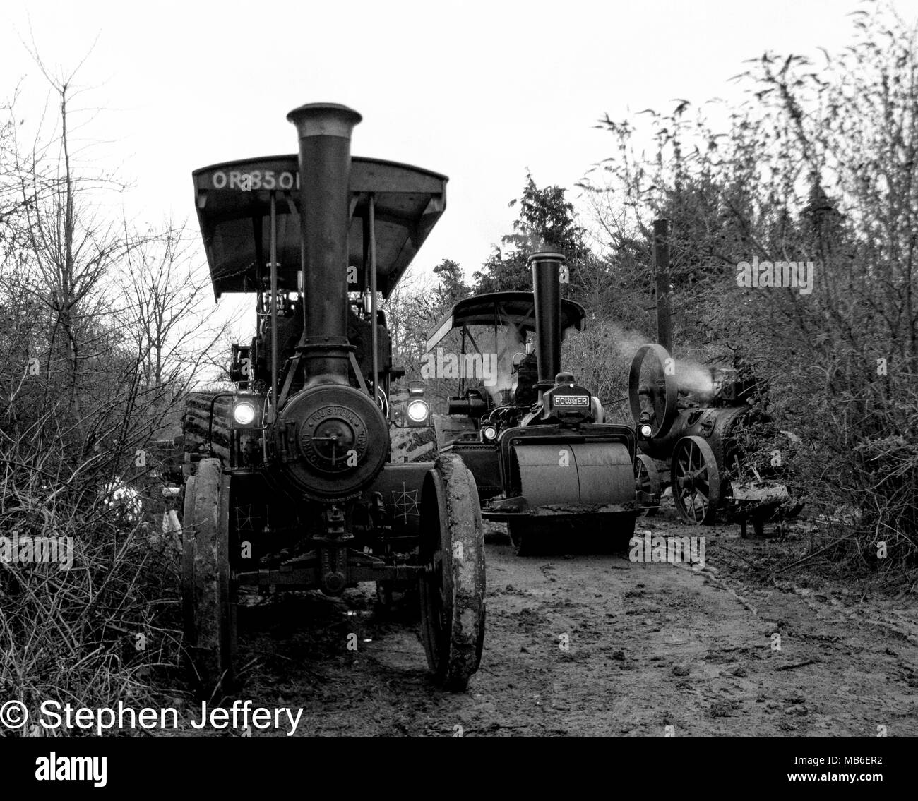 black and white photo of steam traction engines and a portable engien - Stock Image