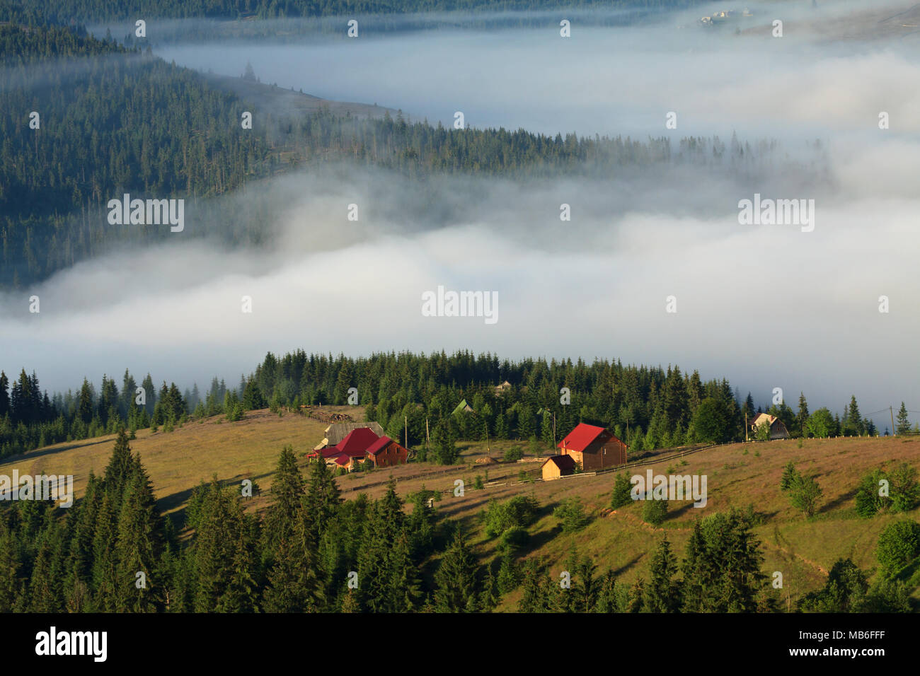 A peaceful village in a valley covered with mists. Apuseni Mountains, Carpathian Region, Romania. - Stock Image