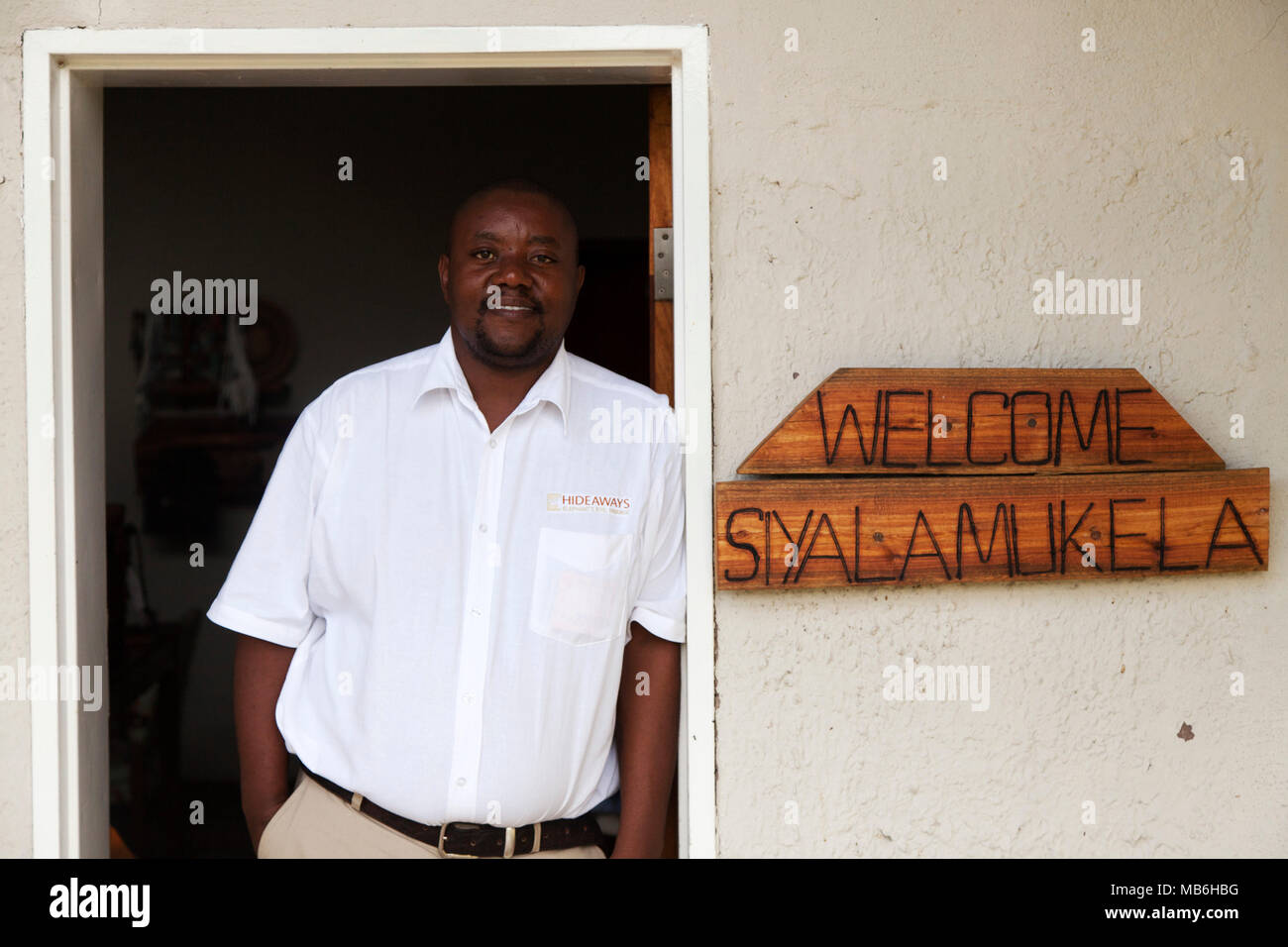 Staff member at the Elephant Eye Safari Lodge in Hwange National Park, Zimbabwe. The man leans against a door frame by a sign welcoming guests. - Stock Image