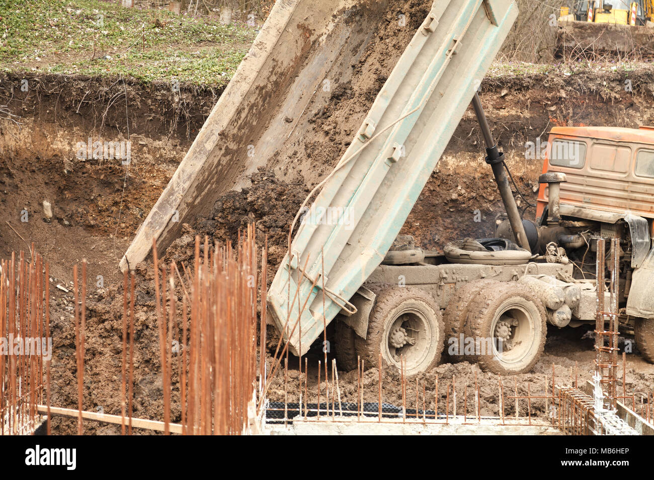 A large truck unloads clay and earth on the construction of a large house - Stock Image