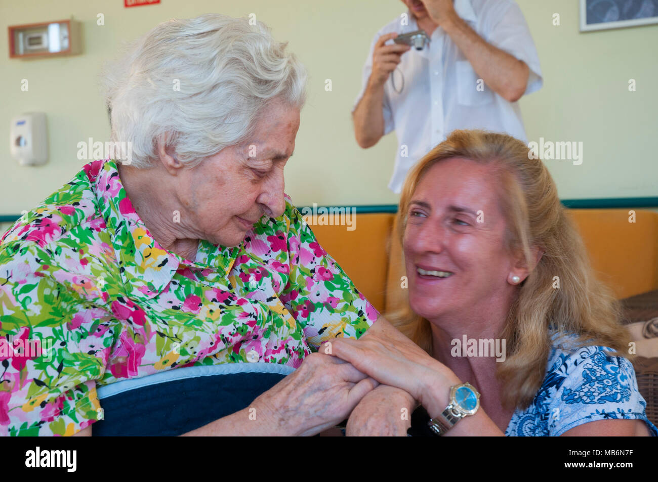 Old lady and mature woman looking at each other and smiling. - Stock Image