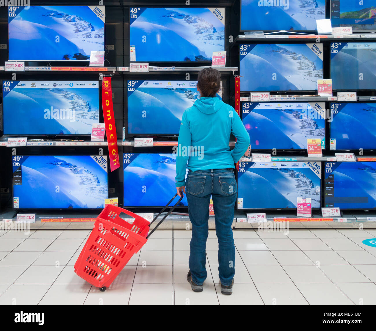 Woman looking at new High definition TV screens in electrical store - Stock Image