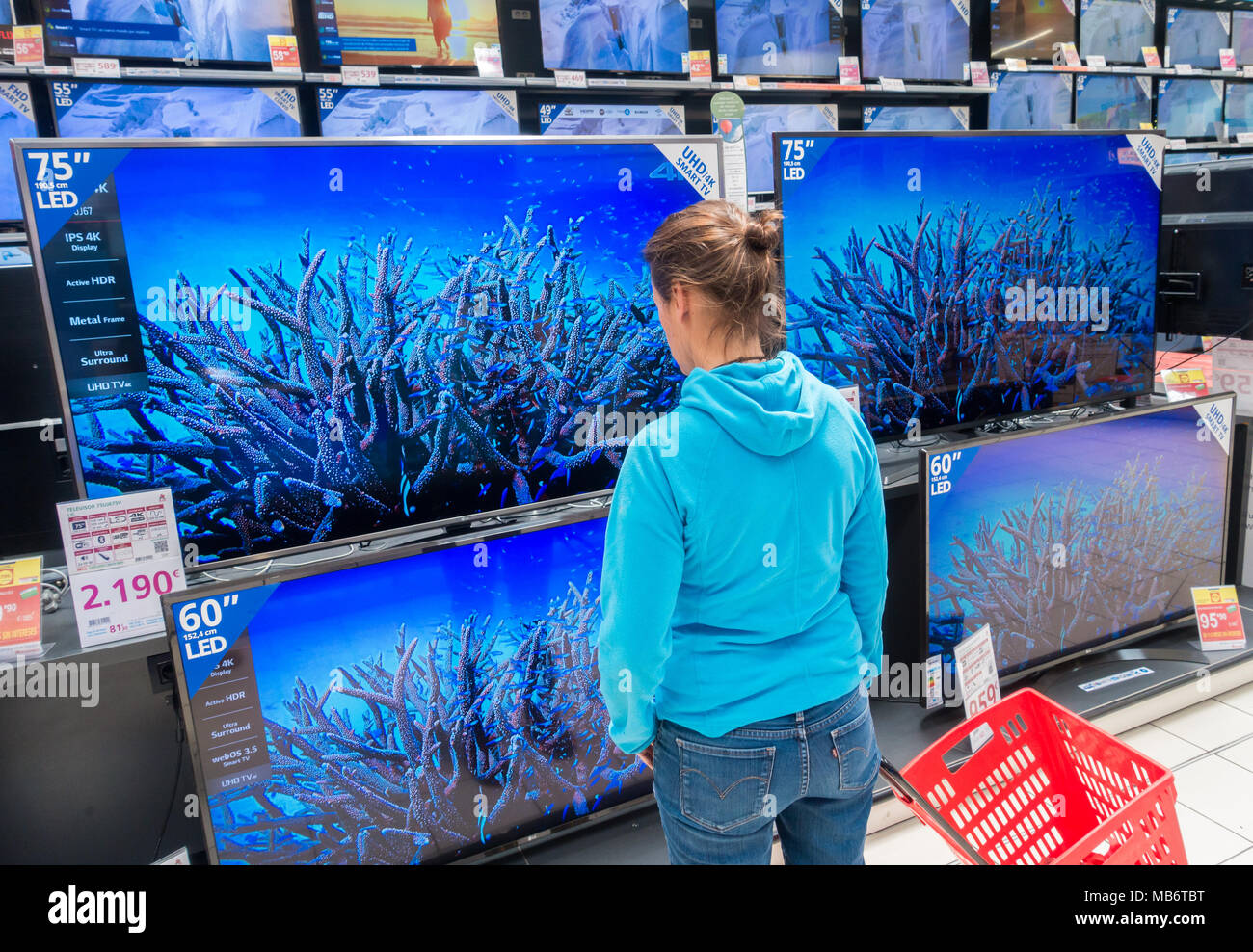 Woman looking at new High definition 4k TV screens in electrical store - Stock Image