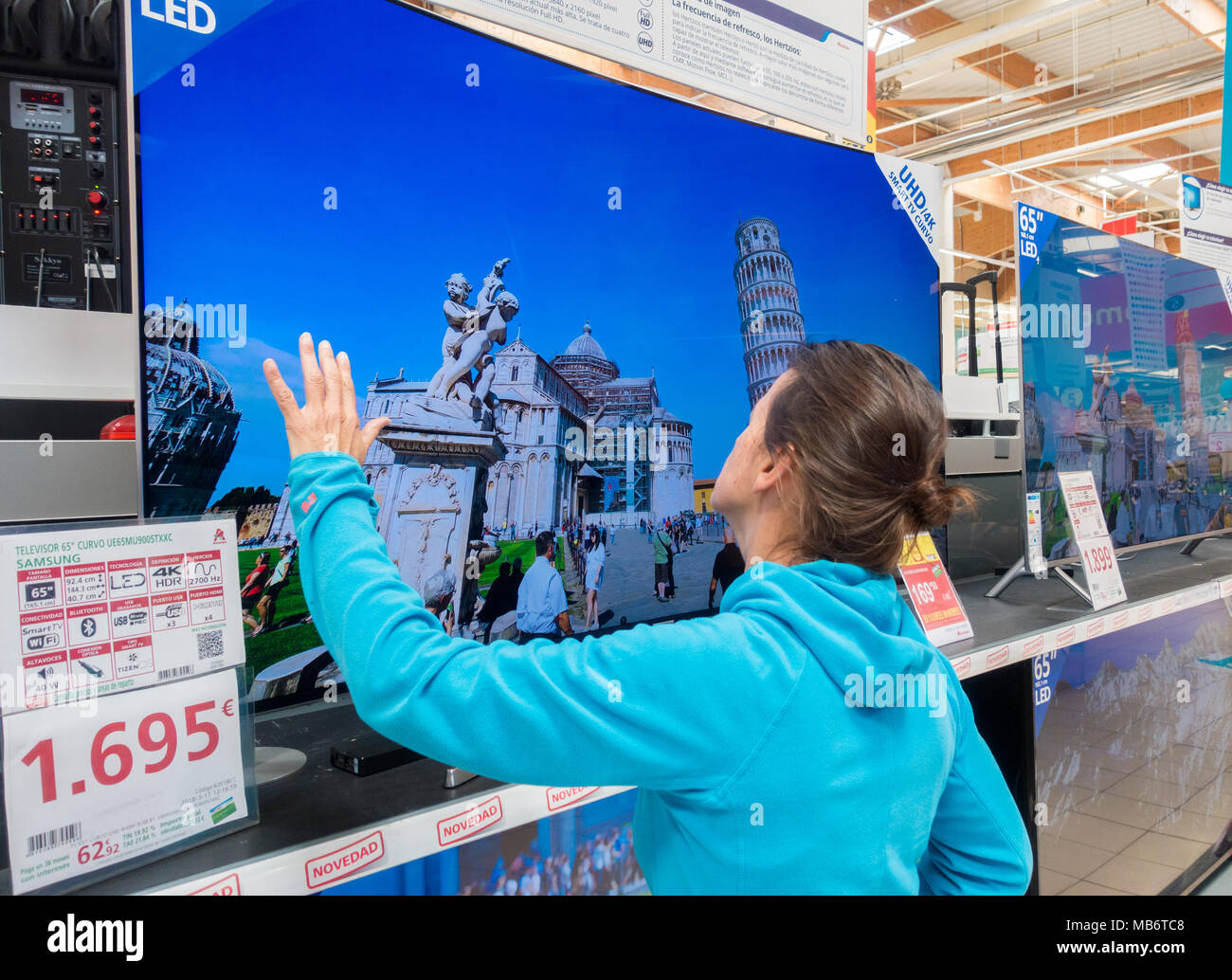 Woman looking at new Samsung High definition 4k curved TV screens in electrical store - Stock Image