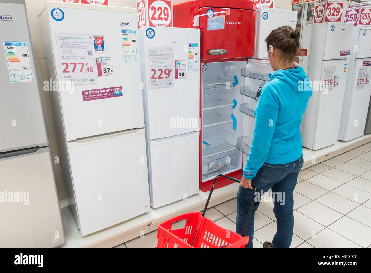 woman looking at new refrigerator/ fridges/fridge freezers in electrical store - Stock Image