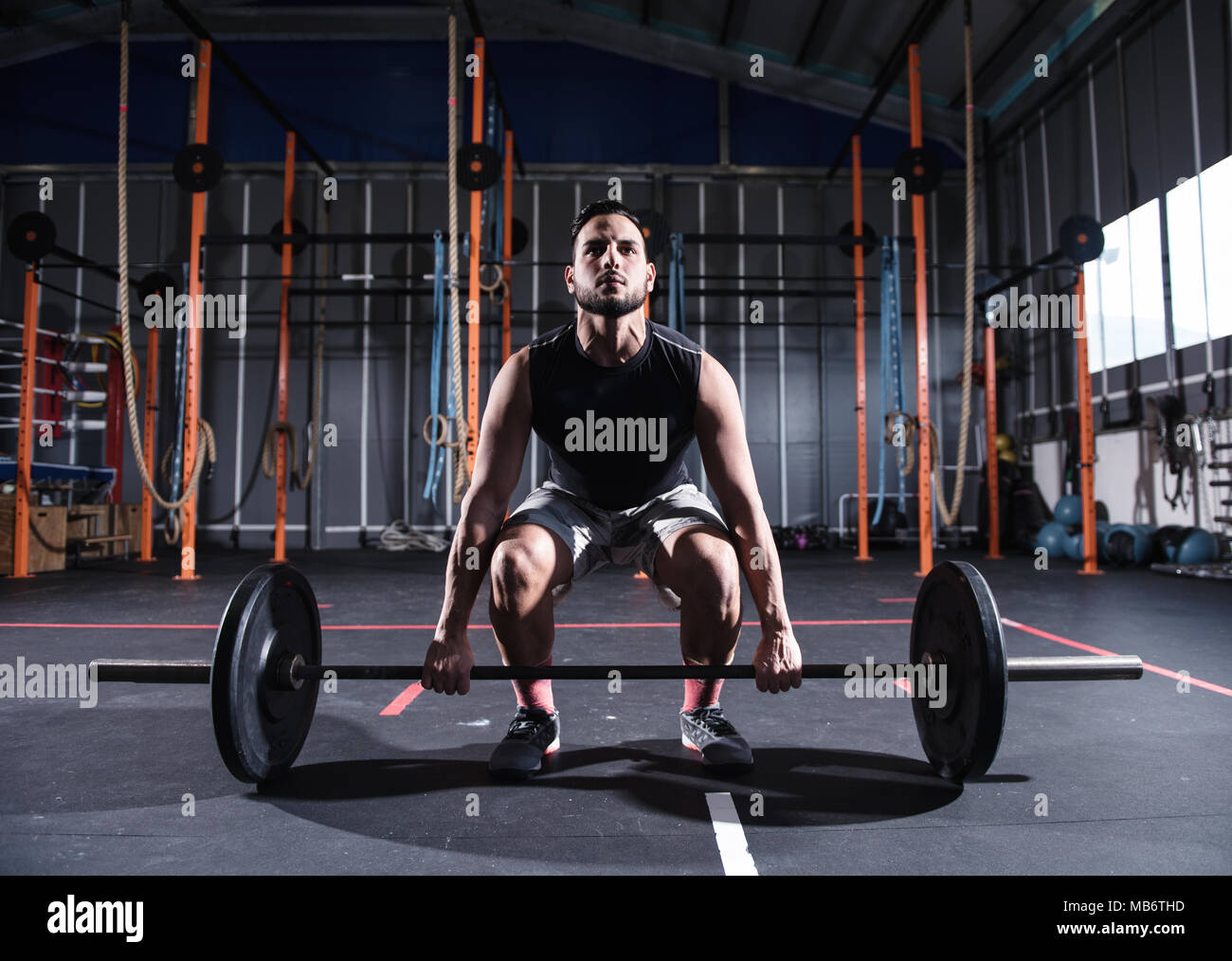 Athletic man works out at the gym with a barbell - Stock Image