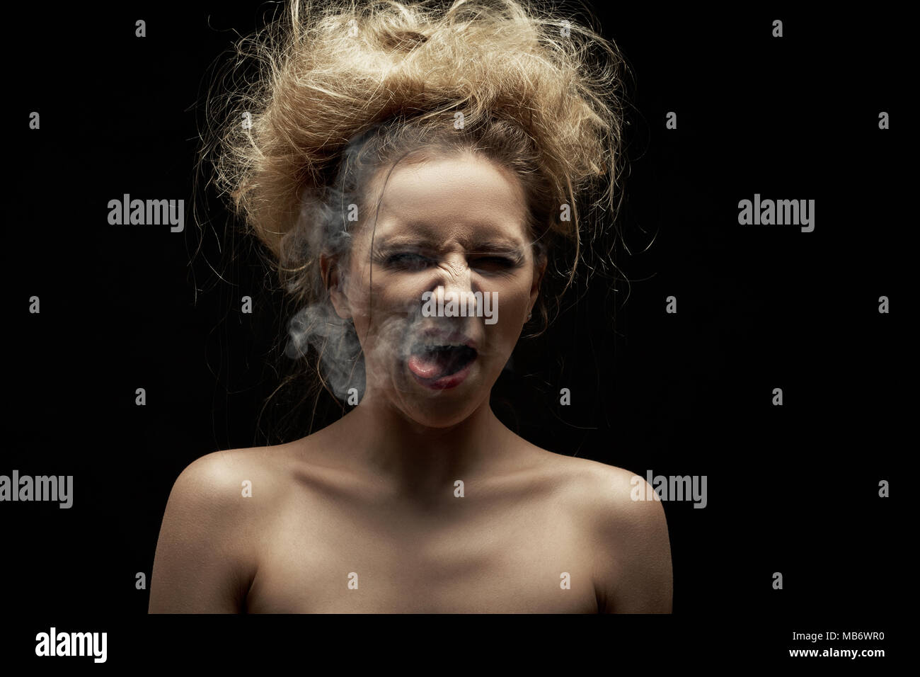 girl coughs from tobacco smoke on black background - Stock Image
