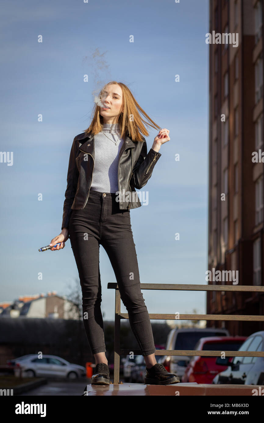young woman smoking electronic cigarette in the city - Stock Image