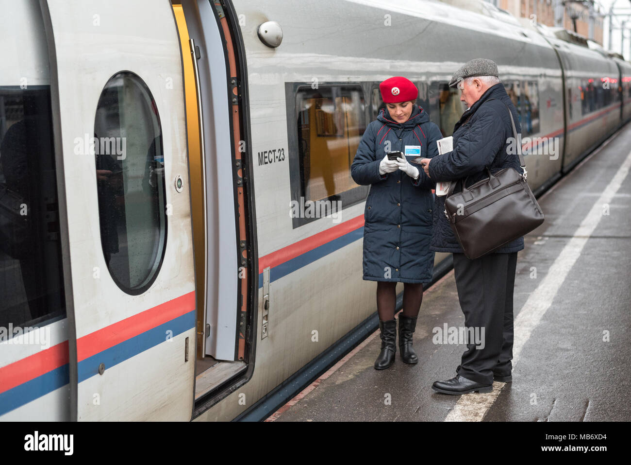 Train conductor (red beret, jacket) of Sapsan train checks in passenger using electronic device at Moskovsky railway station, Saint Petersburg, Russia Stock Photo