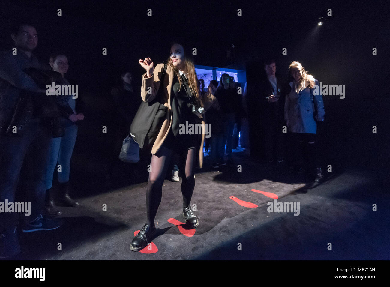 London, UK. 7 April 2018. A woman dances in The Motion Box, a blacked-out space using gesture recognition technology to translate movements into an array of colour and light at 'Sense of Space' an art pop-up which has opened to the public in Broadgate.  Comprising four rooms to challenge the visitor's sensory perceptions through art, the installation is open until 18 May.  Credit: Stephen Chung / Alamy Live News - Stock Image