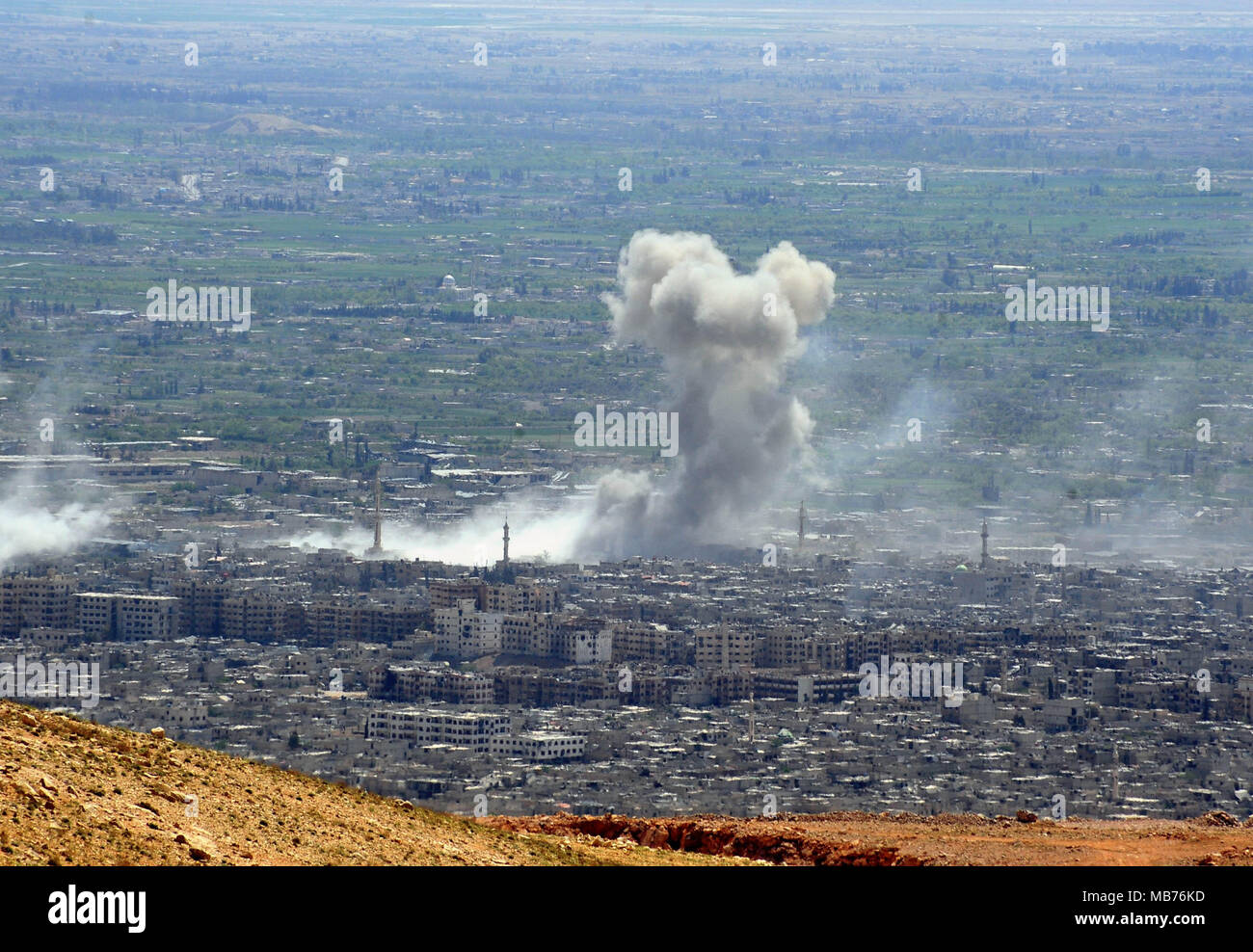 Damascus, Syria. 7th Apr, 2018. Smoke rises after the Syrian army's shelling targeted the Douma district in Eastern Ghouta countryside of Damascus, Syria, on April 7, 2018. The Syrian army on Saturday stormed the frontlines of the Islam Army in the Douma district of the capital Damascus' Eastern Ghouta countryside, state news agency SANA reported. Credit: Ammar Safarjalani/Xinhua/Alamy Live News - Stock Image